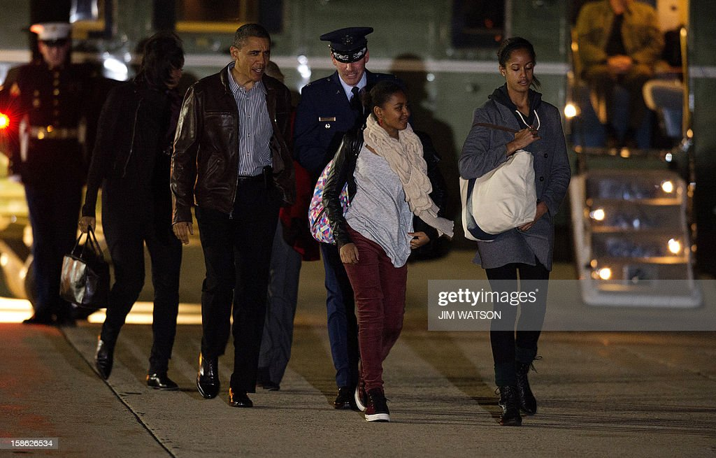 US President Barack Obama (C) and the First family board Air Force One at Andrews Air Force Base, MD, December 21, 2012, en route to Honolulu, Hawaii. US President Barack Obama told lawmakers to go home and drink some Christmas egg nog before coming back to Washington to pass a scaled-down tax package to avert a year-end fiscal crisis. Obama said he still wanted a comprehensive and large deficit-cutting bill to put the US economy on the path to long-term prosperity, but that effort stalled when talks broke down between the White House and House Republicans this week. AFP Photo/Jim WATSON