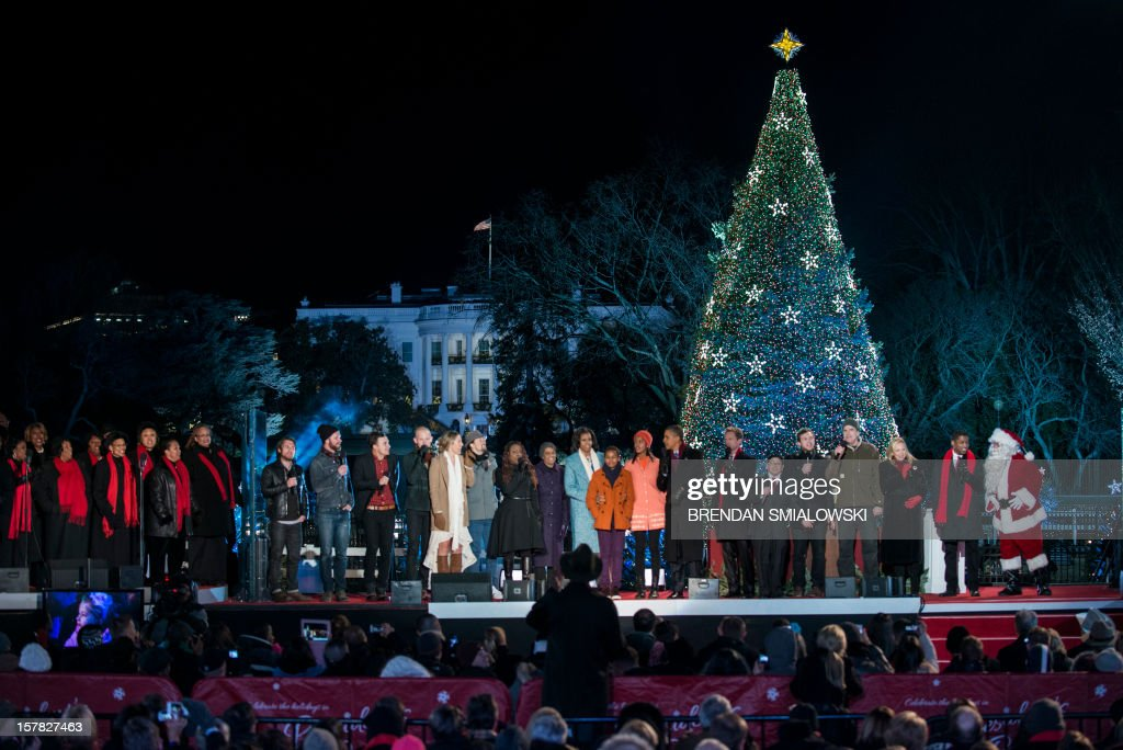US President Barack Obama and the first family join performers while singing during the 90th annual National Christmas Tree Lighting on the Ellipse of the National Mall December 6, 2012 in Washington, DC. Obama and others attended the event which included entertainment before the lighting of the National Christmas Tree. AFP PHOTO/Brendan SMIALOWSKI