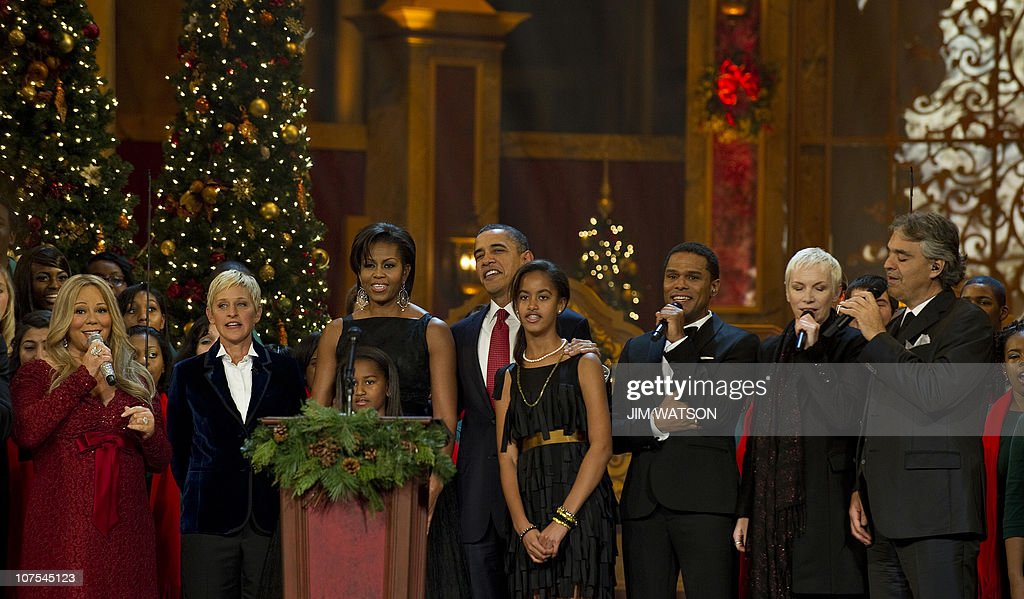 US President Barack Obama (C) and the first family sing with US singer Mariah Carey (L), TV Host Ellen Degeneres (2nd L), Italian Tenor Andrea Bocelli (R), Scottish recording artist Annie Lennox (2nd R), and US R&B singer Maxwell (3rd R) during Christmas in Washington, a charitable fundraiser and musical celebration of the holidays, at the National Building Museum in Washington, DC, December 12, 2010. AFP PHOTO/Jim WATSON