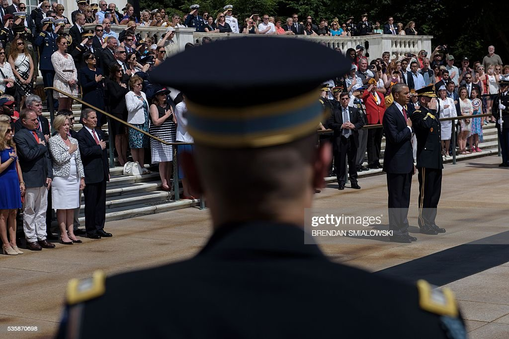 US President Barack Obama (2R) and US Major General Bradley A. Becker (R), Commander of the Military District of Washington, listen to Taps after placing a wreath at the Tomb of the Unknowns to honor Memorial Day at Arlington National Cemetery May 30, 2016 in Arlington, Virginia. / AFP / Brendan Smialowski