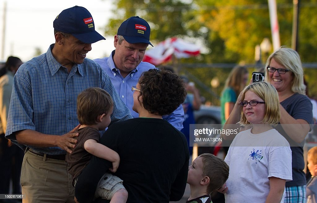 US President Barack Obama (L) and US Secretary of Agriculture Tom Vilsack (C) greet people as they visit the Iowa State Fair in Des Moines, Iowa, on August 13, 2012 during an unannounced stop on his three-day campaign bus tour. AFP PHOTO/Jim WATSON