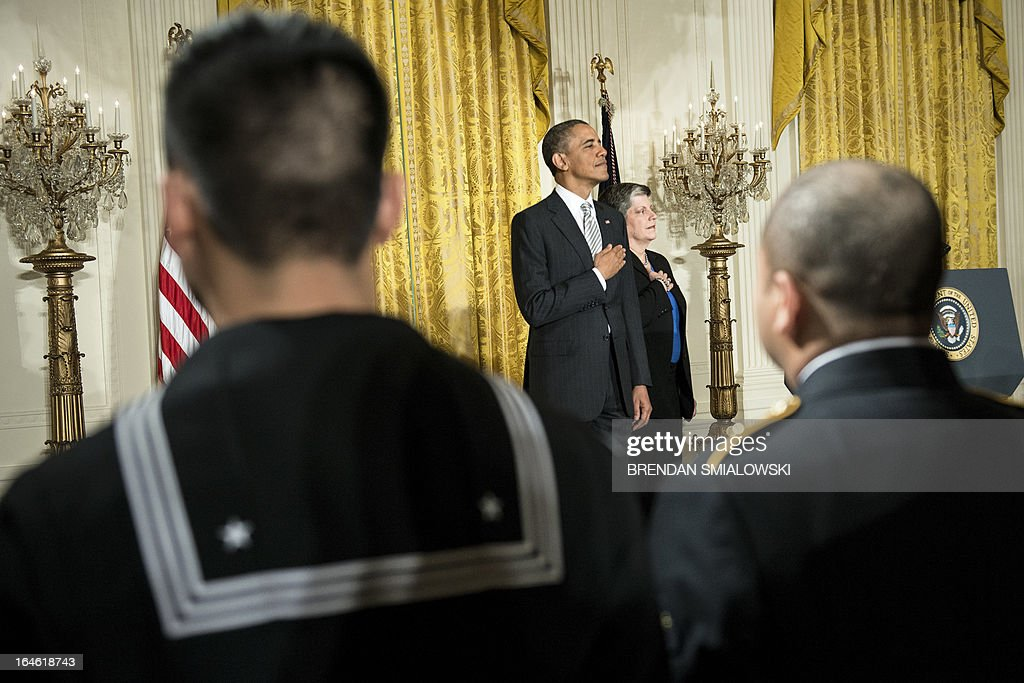 US President Barack Obama and US Secretary of Homeland Security Janet Napolitano listen to the national anthem during a naturalization ceremony in the East Room of the White House on March 25, 2013 in Washington. Obama presided while Napolitano administered the oath of allegiance to active duty service members and civilians officially granting them United States citizenship. AFP PHOTO/Brendan SMIALOWSKI