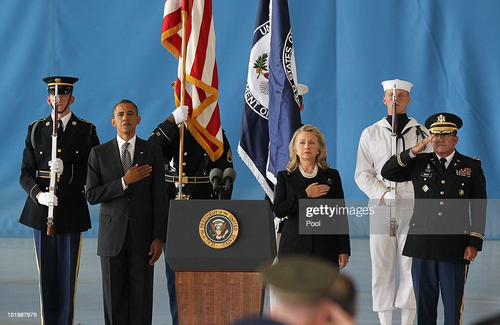 S President Barack Obama and US Secretary of State Hillary Clinton hold their hands over their hearts during the Transfer of Remains Ceremony for the...