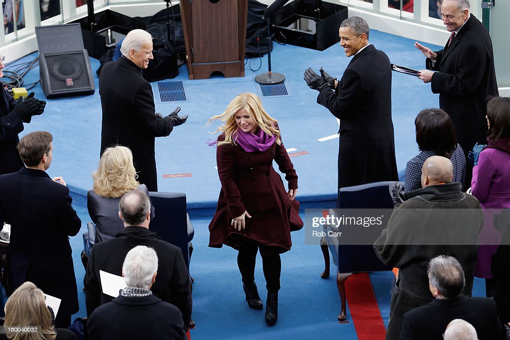 U.S. President Barack Obama (R) and U.S. Vice President Joe Biden (L) applaud after singer Kelly Clarkson finished her performance of 'My Country, 'Tis of Thee' during the public ceremonial inauguration on the West Front of the U.S. Capitol January 21, 2013 in Washington, DC. Barack Obama was re-elected for a second term as President of the United States.