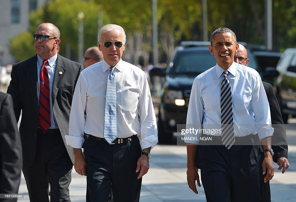 US President Barack Obama and US Vice President Joe Biden walk on Pennsylvania Avenue from the White House to get lunch at a nearby deli in Washington, DC on October 4, 2013. Obama walked over to the deli with US Vice President Joe Biden and ordered sandwiches to go. AFP PHOTO/Mandel NGAN