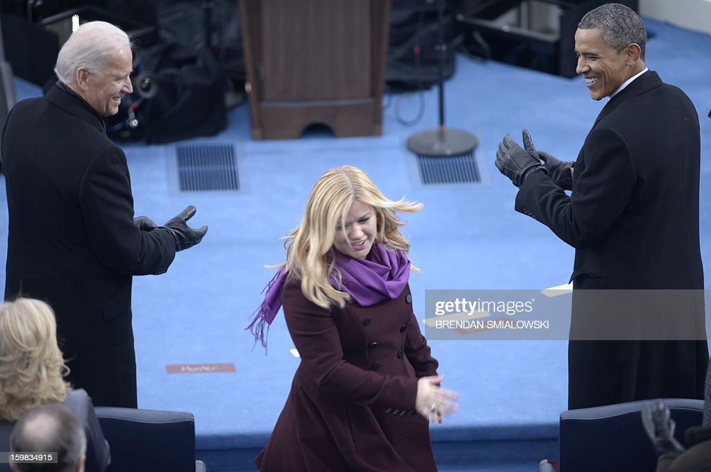US President Barack Obama (R) and Vice President Joe Biden (L) smile at singer Kelly Clarkson (C) after Obama took the oath of office during the 57th Presidential Inauguration ceremonial swearing-in at the US Capitol on January 21, 2013 in Washington, DC. The oath was administered by US Supreme Court Chief Justice John Roberts. AFP PHOTO/Brendan SMIALOWSKI