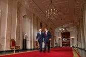 US President Barack Obama and Vice President Joe Biden walk in the Cross Hall of the White House in Washington to the East Room where Obama delivered...