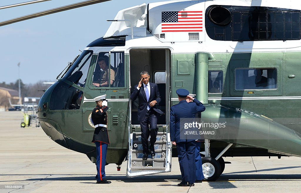 US President Barack Obama (C) arrives to board Air Force One at the Andrews Air Force Base in Maryland on April 3, 2013 en route to Denver, Colorado, where he will continue asking the American people to join him in calling on Congress to pass common-sense measures to reduce gun violence. The president has demanded votes on measures including a requirement for background checks on all gun purchases, limits on high capacity ammunition magazines, a reinstated assault weapons ban, new gun trafficking laws, and new school safety plans. But the assault weapons ban push appears certain to fail to get sufficient support in the Senate, following a huge campaign by the gun lobby and opposition from Republicans and Democrats from conservative and rural areas. AFP PHOTO/Jewel Samad