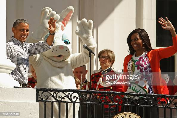 President Barack Obama as a person dressed as the Easter Bunny and first lady Michelle Obama wave to visitors from the Truman Balcony during the...