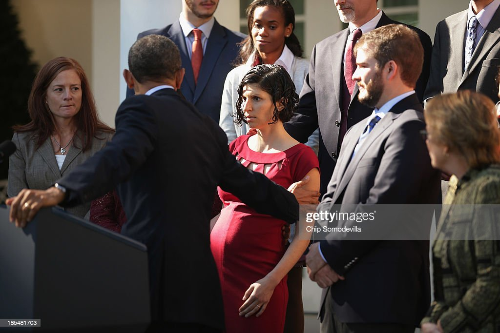 U.S. President <a gi-track='captionPersonalityLinkClicked' href=/galleries/search?phrase=Barack+Obama&family=editorial&specificpeople=203260 ng-click='$event.stopPropagation()'>Barack Obama</a> assists a woman who became dizzy during his remarks about the error-plagued launch of the Affordable Care Act's online enrollment in the Rose Garden of the White House October 21, 2013 in Washington, DC. According to the White House, the president was joined by 'consumers, small business owners, and pharmacists who have either benefitted from the health care law already or are helping consumers learn about what the law means for them and how they can get covered. 'Despite the new health care law's website problems, Obama urged Americans not to be deterred from registering for Obamacare because of the technological problems that have plagued its rollout.