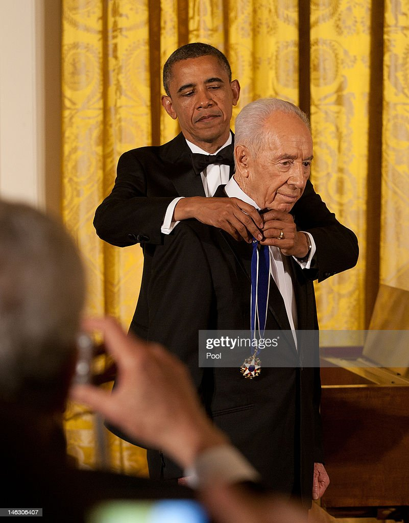 U.S. President <a gi-track='captionPersonalityLinkClicked' href=/galleries/search?phrase=Barack+Obama&family=editorial&specificpeople=203260 ng-click='$event.stopPropagation()'>Barack Obama</a> awards the Presidential Medal of Freedom to Israeli President <a gi-track='captionPersonalityLinkClicked' href=/galleries/search?phrase=Shimon+Peres&family=editorial&specificpeople=201775 ng-click='$event.stopPropagation()'>Shimon Peres</a> during a dinner in his honor in the East Room of the White House, in Washington, on June 13, 2012 in Washington, D.C. Peres is the second Israeli, after Natan Sharansky, to receive the Presidential Medal of Freedom.