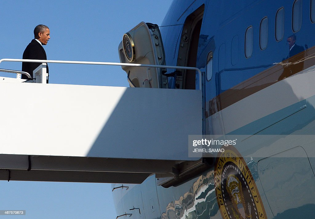 US President Barack Obama boards Air Force One at Andrews Air Force Base in Maryland on February 7 2014 en route to Lansing Michigan Obama is...