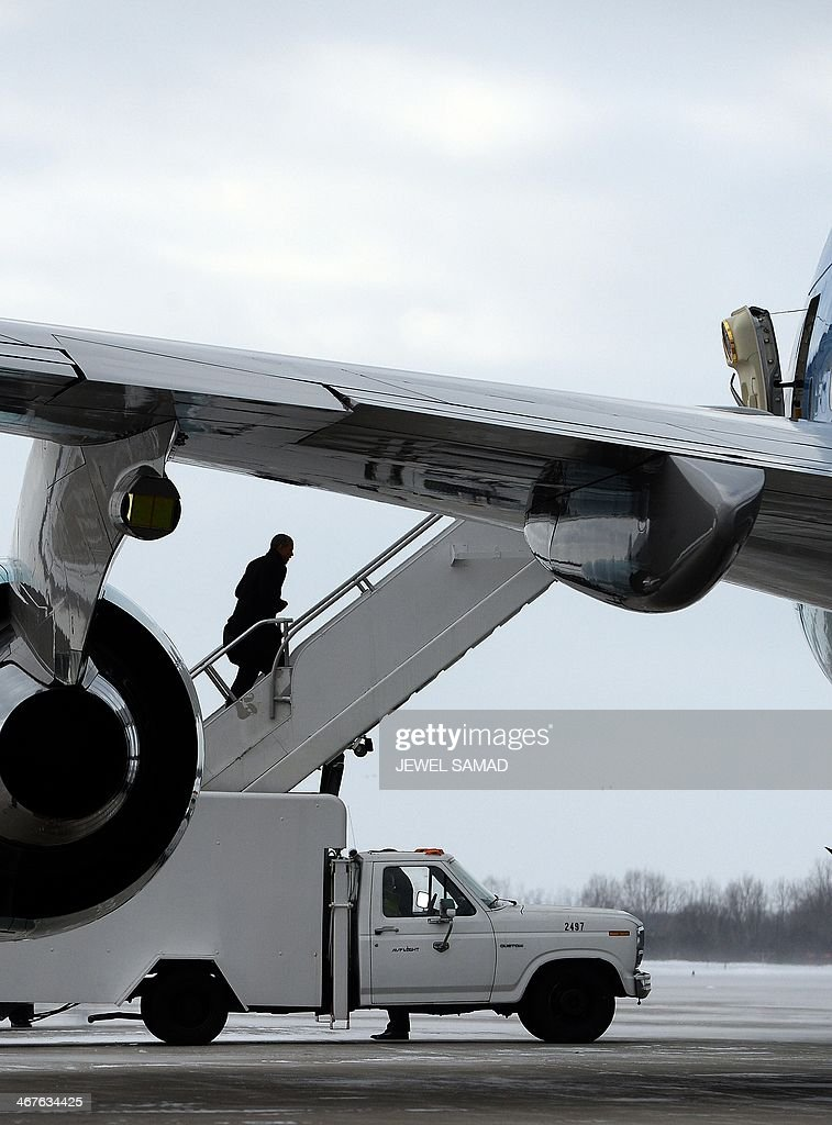 US President Barack Obama boards Air Force One at Capital Region International Airport in Lansing Michigan on February 7 2014 to leave Michigan where...