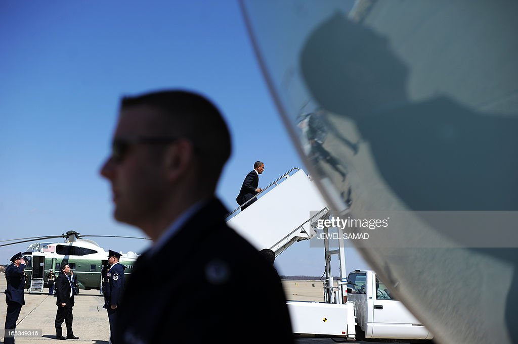 US President Barack Obama (C) boards Air Force One at the Andrews Air Force Base in Maryland on April 3, 2013 en route to Denver, Colorado, where he will continue asking the American people to join him in calling on Congress to pass common-sense measures to reduce gun violence. The president has demanded votes on measures including a requirement for background checks on all gun purchases, limits on high capacity ammunition magazines, a reinstated assault weapons ban, new gun trafficking laws, and new school safety plans. But the assault weapons ban push appears certain to fail to get sufficient support in the Senate, following a huge campaign by the gun lobby and opposition from Republicans and Democrats from conservative and rural areas. AFP PHOTO/Jewel Samad
