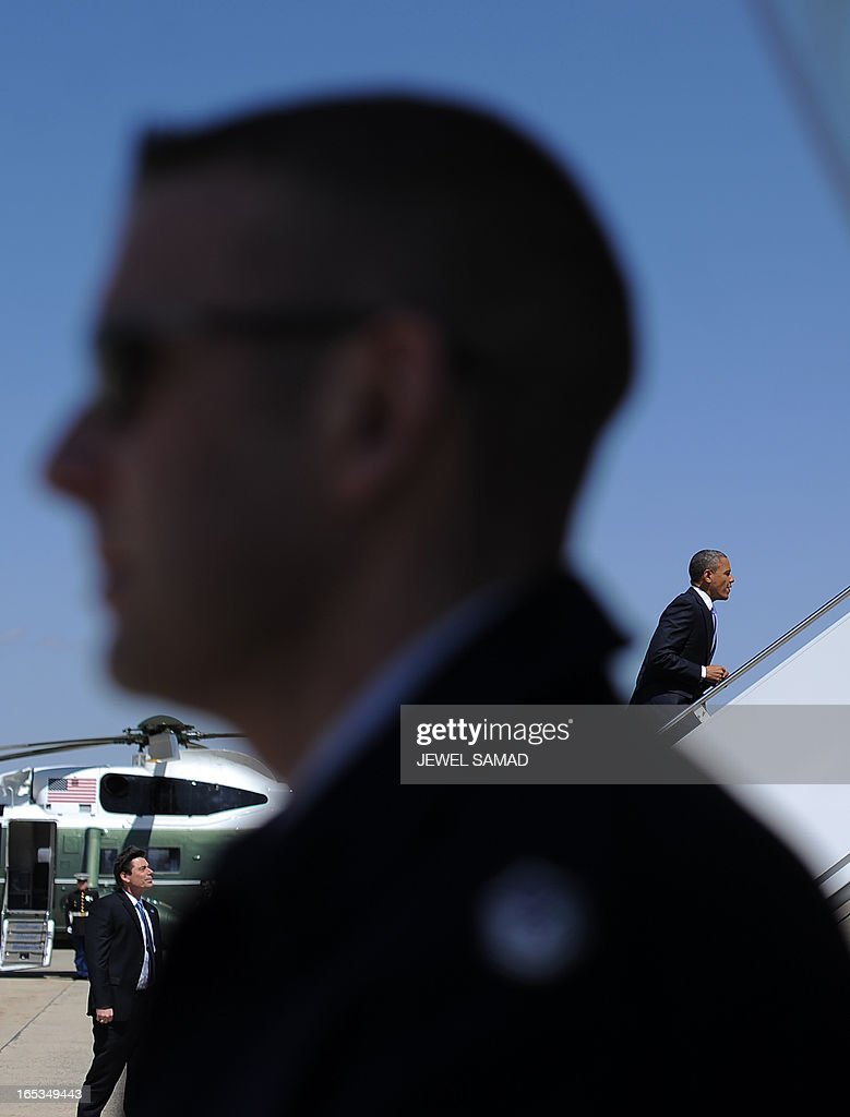 US President Barack Obama (R) boards Air Force One at the Andrews Air Force Base in Maryland on April 3, 2013 en route to Denver, Colorado, where he will continue asking the American people to join him in calling on Congress to pass common-sense measures to reduce gun violence. The president has demanded votes on measures including a requirement for background checks on all gun purchases, limits on high capacity ammunition magazines, a reinstated assault weapons ban, new gun trafficking laws, and new school safety plans. But the assault weapons ban push appears certain to fail to get sufficient support in the Senate, following a huge campaign by the gun lobby and opposition from Republicans and Democrats from conservative and rural areas. AFP PHOTO/Jewel Samad