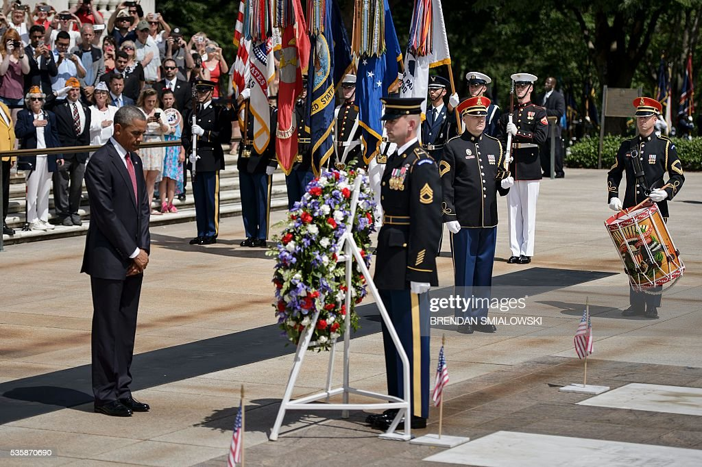 US President Barack Obama (L) bows his head after placing a wreath at the Tomb of the Unknowns to honor Memorial Day at Arlington National Cemetery May 30, 2016 in Arlington, Virginia. / AFP / Brendan Smialowski