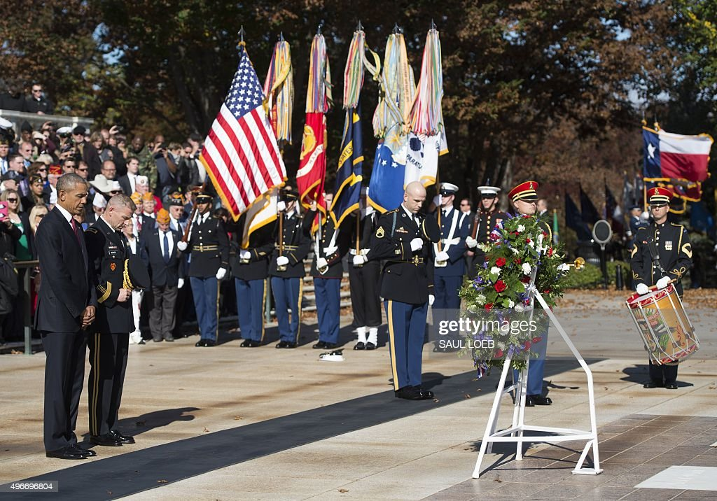 US President Barack Obama bows his head during the playing of taps as he participates in a wreath laying ceremony at the Tomb of the Unknown Soldier...