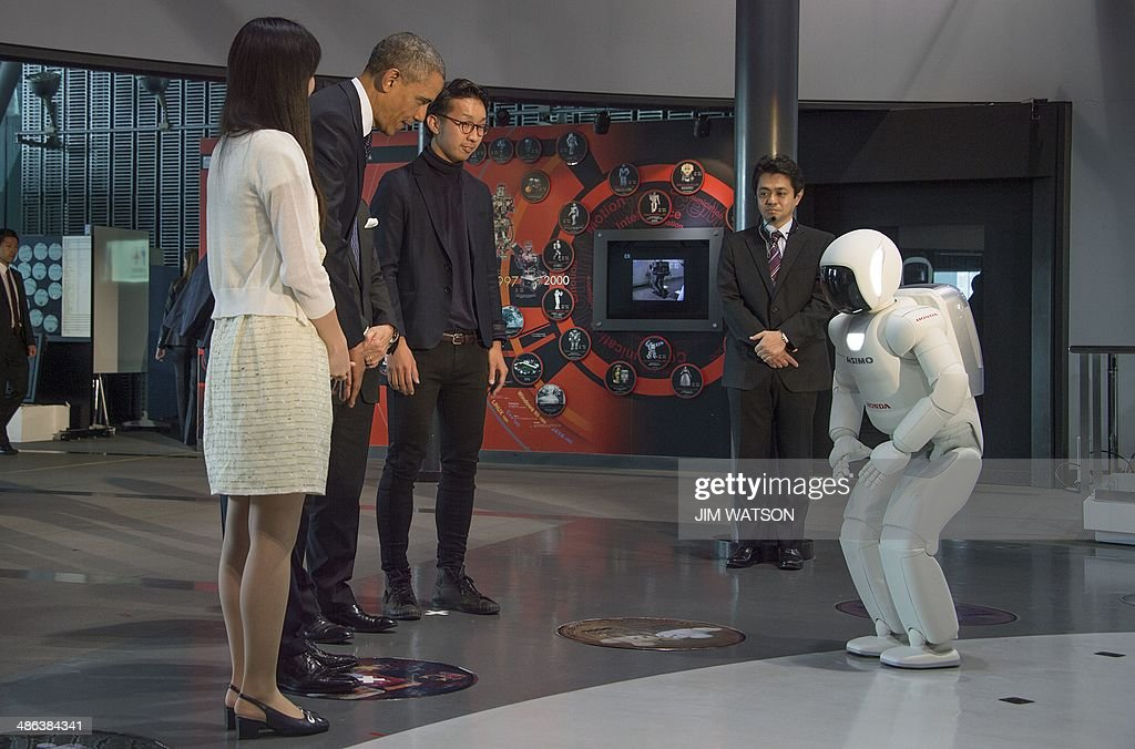 US President Barack Obama (2nd L) bows to Honda's humanoid robot ASIMO (R), an acronym for Advanced Step in Innovative MObility, as he tours the Miraikan Science Expo in Tokyo on April 24, 2014. Obama earlier vowed to defend Japan if China attacks over a tense territorial dispute, but also urged Beijing to help stop North Korea from forging ahead with its 'dangerous' nuclear programme. AFP PHOTO / Jim WATSON