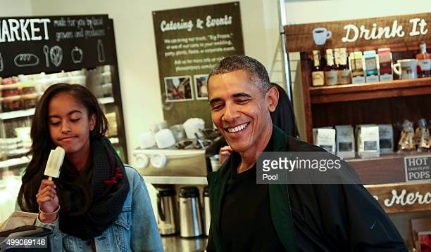 President Barack Obama buys ice cream for his daughters Malia and Sasha at Pleasant Pops during Small Business Saturday on November 28 in Washington...