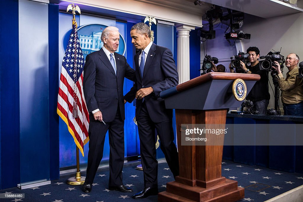 U.S. President Barack Obama, center, and U.S. Vice President Joseph 'Joe' Biden, left, depart after speaking in the Brady Press Briefing Room at the White House in Washington, D.C., U.S., on Tuesday, Jan. 1, 2013. The House of Representatives passed legislation averting income tax increases for most U.S. workers after Republicans abandoned their effort to attach spending cuts that would have been rejected by the Senate. Photographer: Brendan Hoffman/Pool via Bloomberg