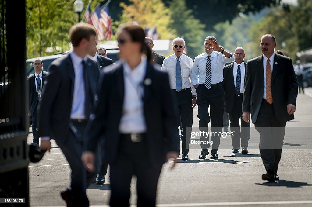 U.S. President Barack Obama, center, and U.S. Vice President Joseph 'Joe' Biden, center left, walk from the White House to a Taylor Gourmet Deli location on Pennsylvania Avenue for a take-out lunch in Washington, D.C., U.S., on Friday, Oct. 4, 2013. Obama canceled plans to attend two economic summits in Asia next week, a setback for his top foreign policy goal, as he remains in Washington to seek an end to the partial government shutdown. Photographer: Pete Marovich/Bloomberg via Getty Images