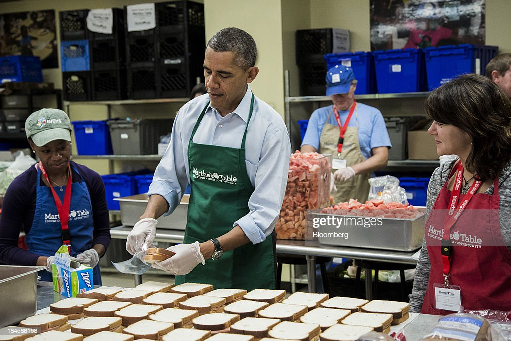 U.S. President Barack Obama, center, helps bag sandwiches while visiting furloughed federal workers volunteering at Martha's Table including Dolly Garcia with the U.S. Census Bureau, right, and Chantelle Burton with the U.S. Department of Health and Human Services department in Washington, D.C., U.S., on Monday, Oct. 14, 2013. Obama summoned the four congressional leaders to the White House today as Senate Majority Leader Harry Reid said lawmakers are closer to ending a partial government shutdown and preventing U.S. borrowing authority from lapsing in three days. Photographer: T.J. Kirkpatrick/Bloomberg via Getty Images