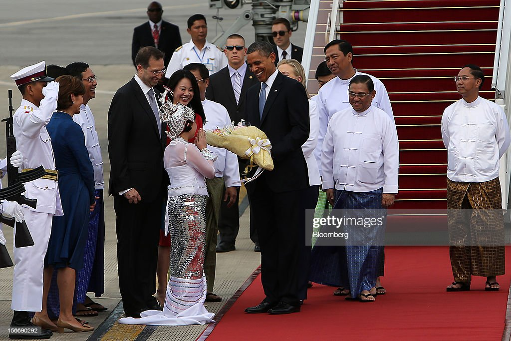 U.S. President Barack Obama, center, receives a bouquet from a Burmese girl on his arrival at Yangon International Airport in Yangon, Myanmar, on Monday, Nov. 19, 2012. Obama hailed Myanmar's shift to democracy and urged more steps to increase freedom in the first visit to the former military regime by a U.S. president. Photographer: Dario Pignatelli/Bloomberg via Getty Images