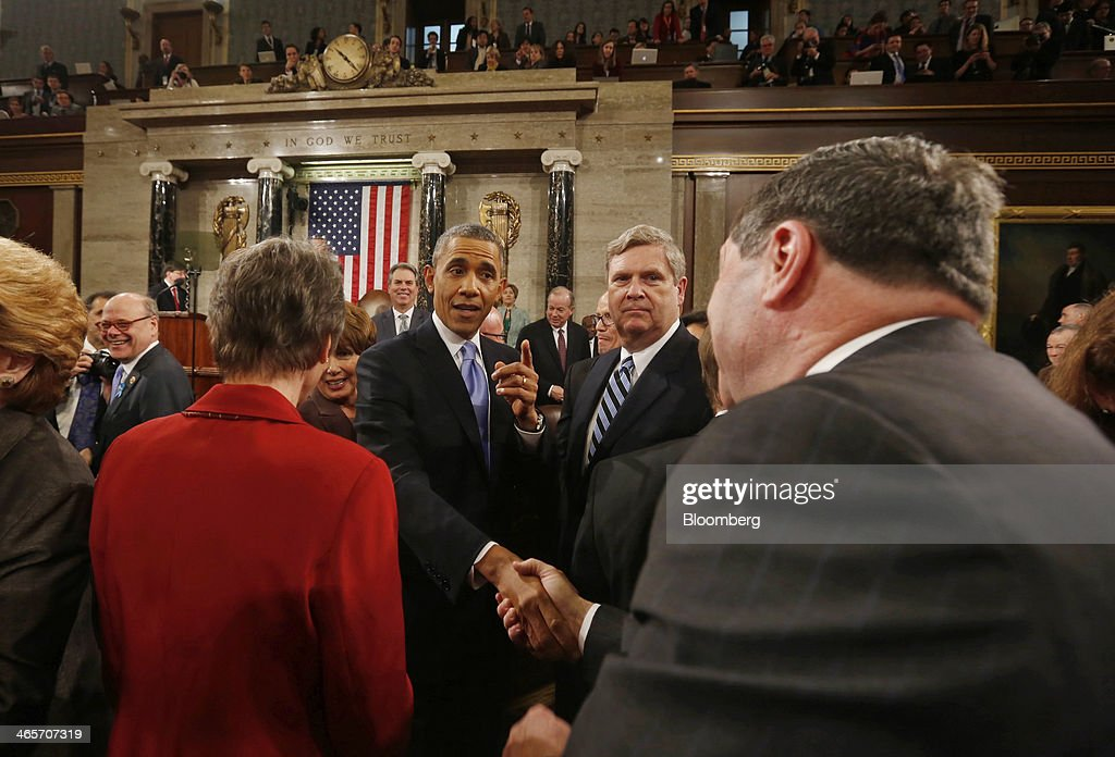 U.S. President Barack Obama, center, shakes hands with an attendee after delivering the State of the Union address to a joint session of Congress at the Capitol in Washington, D.C., U.S., on Tuesday, Jan. 28, 2014. Obama offered modest steps to chip away at the country's economic and social challenges in a State of the Union address that reflects the limits of his power to sway Congress. Photographer: Larry Downing/Pool via Bloomberg
