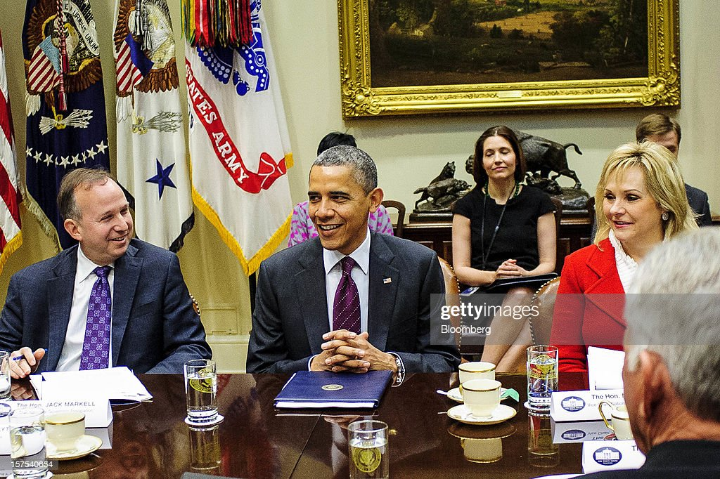 U.S. President Barack Obama, center, speaks while Democrat Jack Markell, governor of Delaware, left, and Republican Mary Fallin, governor of Oklahoma, listen during a meeting with governors in the Roosevelt Room of the White House in Washington, D.C., U.S., on Tuesday, Dec. 4, 2012. Negotiations over the so-called fiscal cliff are stalled as President Obama and Republicans trade offers on ways to avoid more than $600 billion in U.S. spending cuts and tax increases for 2013 that will start to take effect in January if Congress doesn't act. Photographer: Pete Marovich/Bloomberg via Getty Images