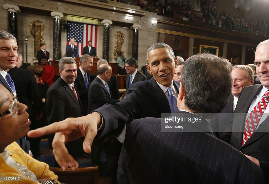 U.S. President Barack Obama, center, speaks with members of Congress as he departs after delivering the State of the Union address at the Capitol in Washington, D.C., U.S., on Tuesday, Jan. 28, 2014. Obama offered modest steps to chip away at the country's economic and social challenges in a State of the Union address that reflects the limits of his power to sway Congress. Photographer: Larry Downing/Pool via Bloomberg