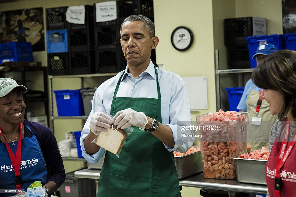 U.S. President Barack Obama, center, tries to close a plastic bag while bagging sandwiches during a visit to furloughed federal workers volunteering at Martha's Table including Dolly Garcia with the U.S. Census Bureau, right, and Chantelle Burton with the U.S. Department of Health and Human Services department in Washington, D.C., U.S., on Monday, Oct. 14, 2013. Obama summoned the four congressional leaders to the White House today as Senate Majority Leader Harry Reid said lawmakers are closer to ending a partial government shutdown and preventing U.S. borrowing authority from lapsing in three days. Photographer: T.J. Kirkpatrick/Bloomberg via Getty Images