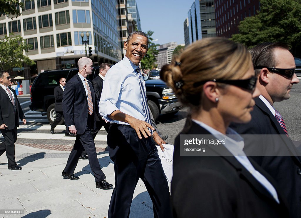 U.S. President Barack Obama, center, walks back to the White House after picking up lunch at a Taylor Gourmet Deli location on Pennsylvania Avenue in Washington, D.C., U.S., on Friday, Oct. 4, 2013. Obama canceled plans to attend two economic summits in Asia next week, a setback for his top foreign policy goal, as he remains in Washington to seek an end to the partial government shutdown. Photographer: Pete Marovich/Bloomberg via Getty Images