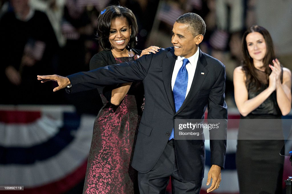 U.S. President <a gi-track='captionPersonalityLinkClicked' href=/galleries/search?phrase=Barack+Obama&family=editorial&specificpeople=203260 ng-click='$event.stopPropagation()'>Barack Obama</a>, center, waves as First Lady <a gi-track='captionPersonalityLinkClicked' href=/galleries/search?phrase=Michelle+Obama&family=editorial&specificpeople=2528864 ng-click='$event.stopPropagation()'>Michelle Obama</a> stands behind him during an election night rally in Chicago, Illinois, U.S., in the early morning on Wednesday, Nov. 7, 2012. Obama, the post-partisan candidate of hope who became the first black U.S. president, won re-election today by overcoming four years of economic discontent with a mix of political populism and electoral math. Photographer: Daniel Acker/Bloomberg via Getty Images
