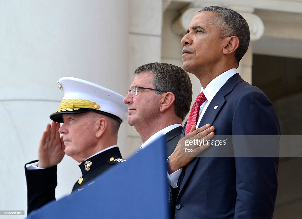 President Barack Obama, Chairman of the Joint Chiefs of Staff Gen. Joseph Dunford (L) and Defense Secretary Ashton Carter (C) listen to the National Anthem at the conclusion of remarks at Arlington National Cemetery on May 30, 2016 in Arlington, Virginia. Obama paid tribute to the nation's fallen military service members.