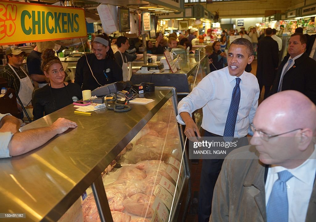 US President Barack Obama chats with a shopkeeper during a visit to Cleveland's West Side Market on October 5, 2012. Obama was in Cleveland for a campaign rallly. AFPHOTO/Mandel NGAN
