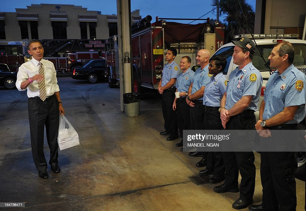 US President Barack Obama chats with firefighters before dropping off doughnuts at a fire station in Tampa, Florida, on October 25, 2012. Obama pursued the sunset west then turned around and chased the dawn, streaking across America on an eight-state marathon as his re-election bid hit top gear. AFP PHOTO / Mandel NGAN