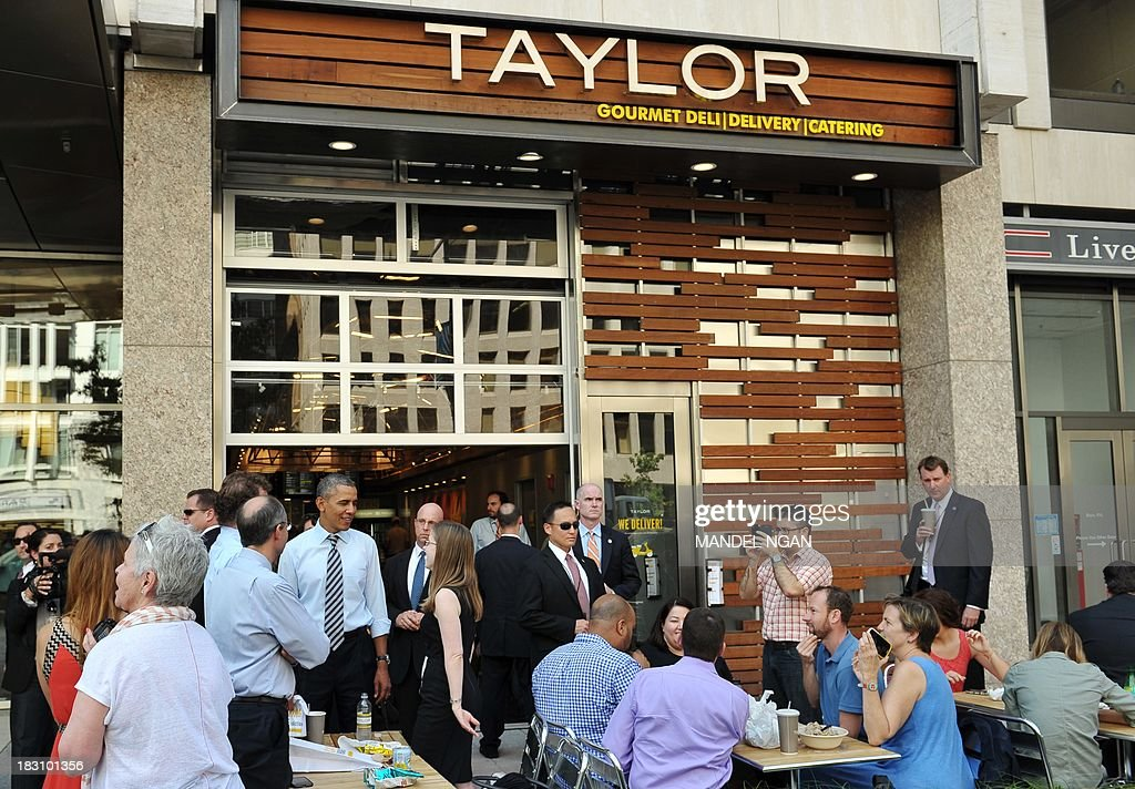 US President Barack Obama (Lower L) chats with patrons outside of Taylor Gourmet Deli on Pennsylvania Ave in Washington, DC on October 4, 2013. Obama walked over to the deli with US Vice President Joe Biden and ordered sandwiches to go. AFP PHOTO/Mandel NGAN