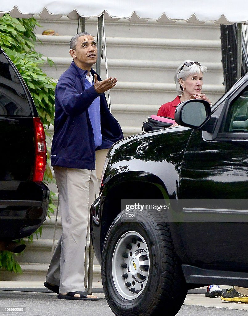 U.S. President Barack Obama checks for rain alongside U.S. Secretary of Health and Human Services Kathleen Sebelius as they depart the South Portico of the White House on May 18, 2013 in Washington, DC. Obama was leaving for a round of golf with Sebelius.