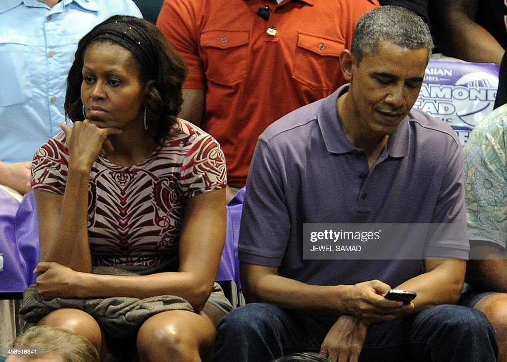 US President Barack Obama checks his cell phone as he and First Lady Michelle Obama watch the Oregon State University vs University of Akron college basketball game at the Diamond Head Classic at the Stan Sheriff Center in Honolulu, Hawaii, on December 22, 2013. Michelle Obama's bother, Craig Robinson, is the coach of Oregon State. The first family is in Hawaii for their annual winter holiday vacation. AFP PHOTO/Jewel SAMAD