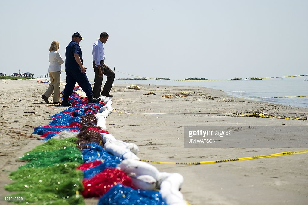 US President Barack Obama (R), Coast Guard Commandant charged with overseeing the oil spill response Admiral Thad Allen (C) and LaFourche Parish President Charlotte Randolph (L) step over boom as they tour Port Fourchon Beach, Louisiana, on May 28, 2010 before a briefing on the federal government's response to the Gulf Coast oil spill. bama arrived in Louisiana to view the oil spill response amid suspense over the latest bid to cap the massive leak in the Gulf of Mexico. AFP PHOTO/Jim WATSON