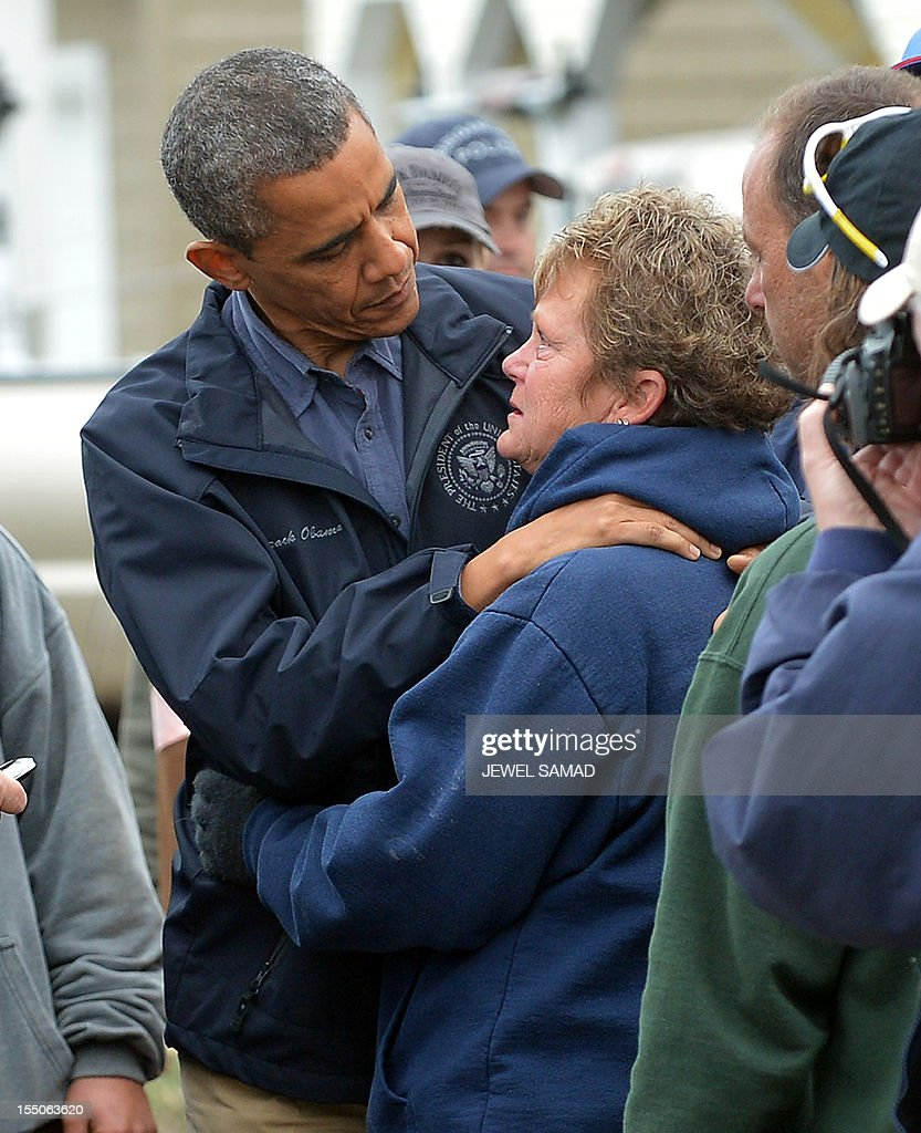US President Barack Obama comforts Hurricane Sandy victim Dana Vanzant as he visits a neighborhood in Brigantine, New Jersey, on October 31, 2012. Americans sifted through the wreckage of superstorm Sandy on Wednesday as millions remained without power. The storm carved a trail of devastation across New York City and New Jersey, killing dozens of people in several states, swamping miles of coastline, and throwing the tied-up White House race into disarray just days before the vote. AFP PHOTO/Jewel Samad