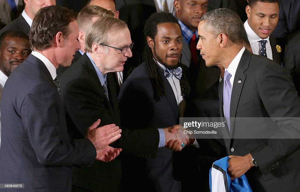 U.S. President Barack Obama (2nd R) congratulates Seattle Seahawks owner Paul Allen (2nd L) as cornerback Richard Sherman (C) looks on during a ceremony honoring the players, coaches and executives of the Super Bowl XLVIII champions in the East Room of the White House May 21, 2014 in Washington, DC. Obama honored the Seahawks and their 43-8 win over the Denver Broncos last February.