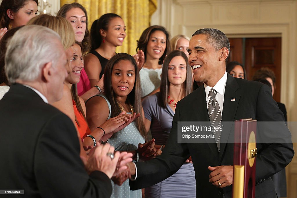 President Barack Obama (R) congratulates the 2013 NCAA champion University of Connecticut Huskies Women's basketball players in the East Room of the White House July 31, 2013 in Washington, DC. Obama hosted the team after they defeated the University of Louisville on April 9 to win their eighth national championship.