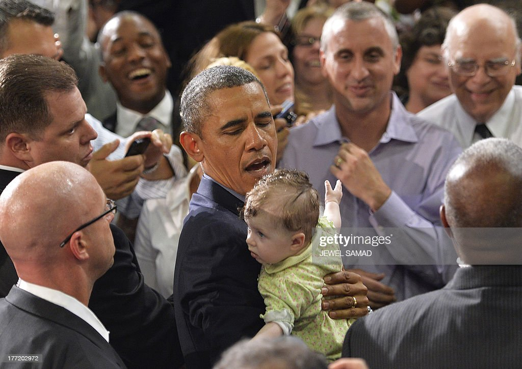 US President Barack Obama cradels a baby after speaking on education at University of Buffalo, the State University of New York, on August 22, 2013 in Buffalo, New York. Obama is on a two-day bus tour through New York and Pennsylvania to discuss his plan to make college more affordable, tackle rising costs, and improve value for students and their families. AFP Photo/Jewel Samad