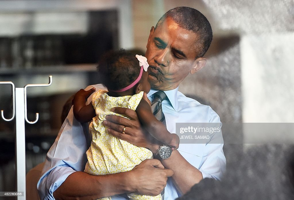 US President Barack Obama cradles a baby as he arrives July 17, 2014 at Charcoal Pit restaurant in Wilmington, Delaware to have lunch with a woman who wrote a letter to him. AFP PHOTO Jewel Samad