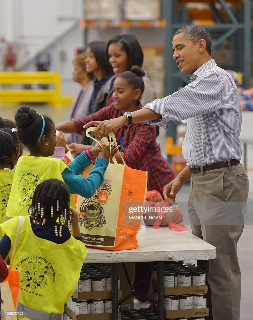 US President Barack Obama, daughter Sasha, First Lady Michelle Obama, daughter Malia and mother-in-law Marian Robinson, distribute food at the Capitol Area Food Bank on November 21, 2012, a day ahead of Thanksgiving, in Washington, DC. AFP PHOTO/Mandel NGAN