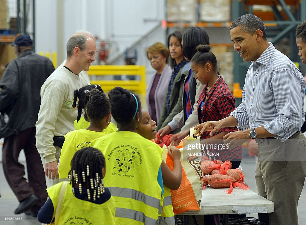 US President Barack Obama, daughters Sasha and Malia, First Lady Michelle Obama, and mother-in-law Marian Robinson, distribute food items at the Capitol Area Food Bank on November 21, 2012, a day ahead of Thanksgiving, in Washington, DC. AFP PHOTO/Mandel NGAN