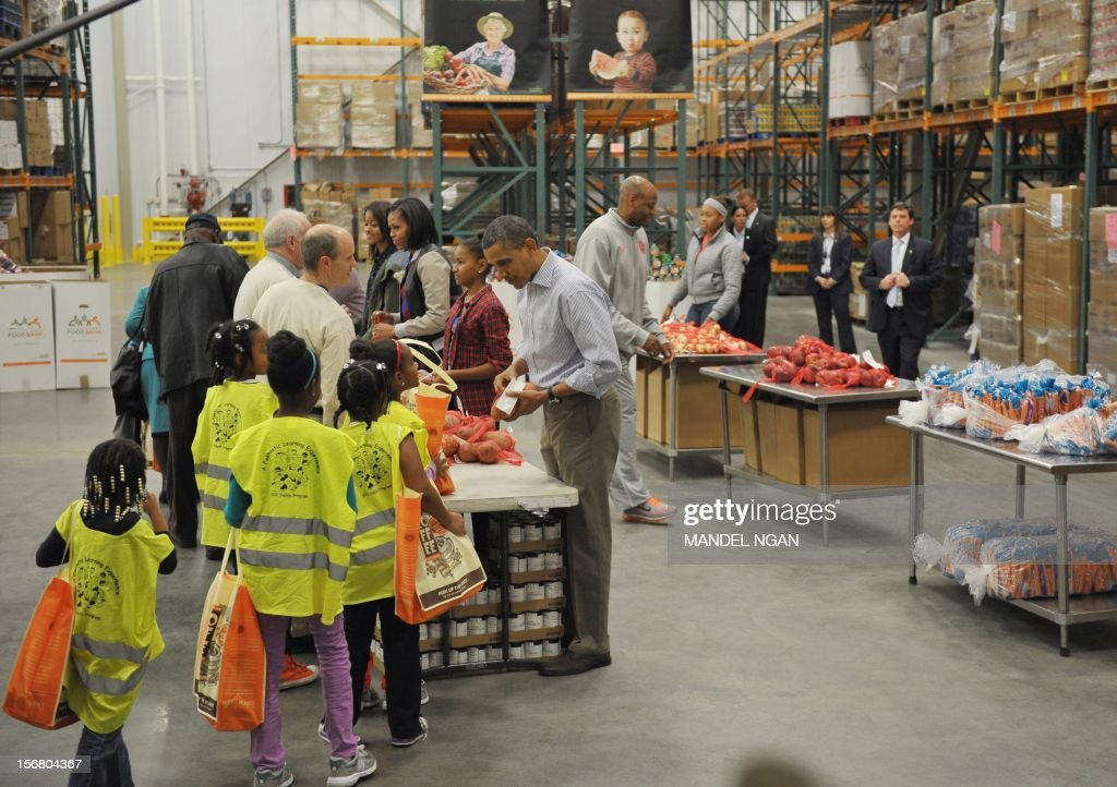 US President Barack Obama, daughters Sasha, First Lady Michelle Obama and daughter Malia distribute food items at the Capitol Area Food Bank on November 21, 2012, a day ahead of Thanksgiving, in Washington, DC. AFP PHOTO/Mandel NGAN