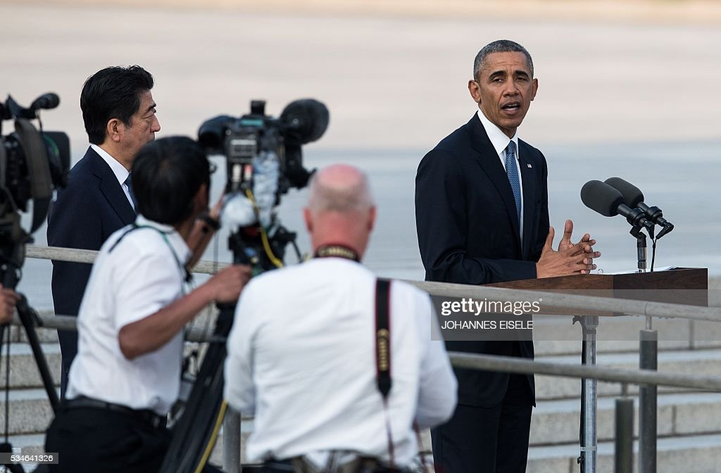 US President Barack Obama (R) delivers a speech as Japanese Prime Minister Shinzo Abe (L) listens at the Hiroshima Peace Memorial park cenotaph in Hiroshima on May 27, 2016. Obama became the first sitting US leader to visit the site that ushered in the age of nuclear conflict. / AFP / JOHANNES