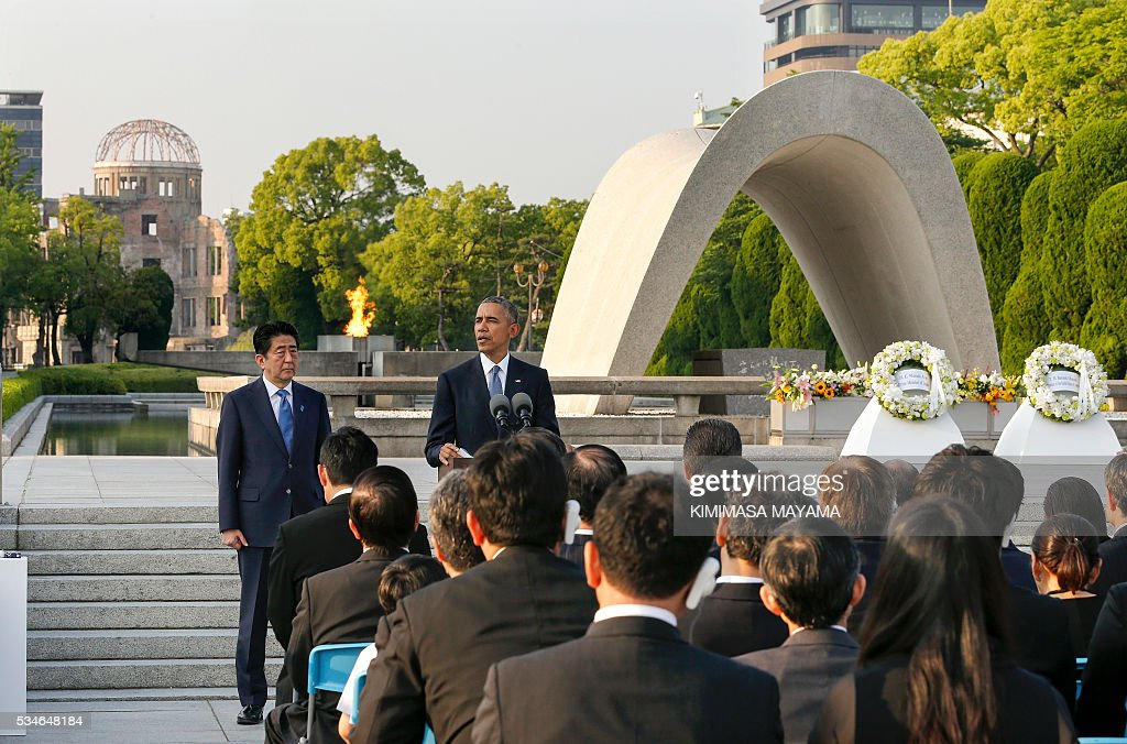 US Presdent Barack Obama (C) delivers his speech next to Japanese Prime Minister Shinzo Abe (L) after laying wreaths at the cenotaph to offer a prayer for victims of the atomic bombing in 1945, at Hiroshima Peace Memorial Park in Hiroshima on May 27, 2016. Obama on May 27 paid moving tribute to victims of the world's first nuclear attack. / AFP / POOL / KIMIMASA